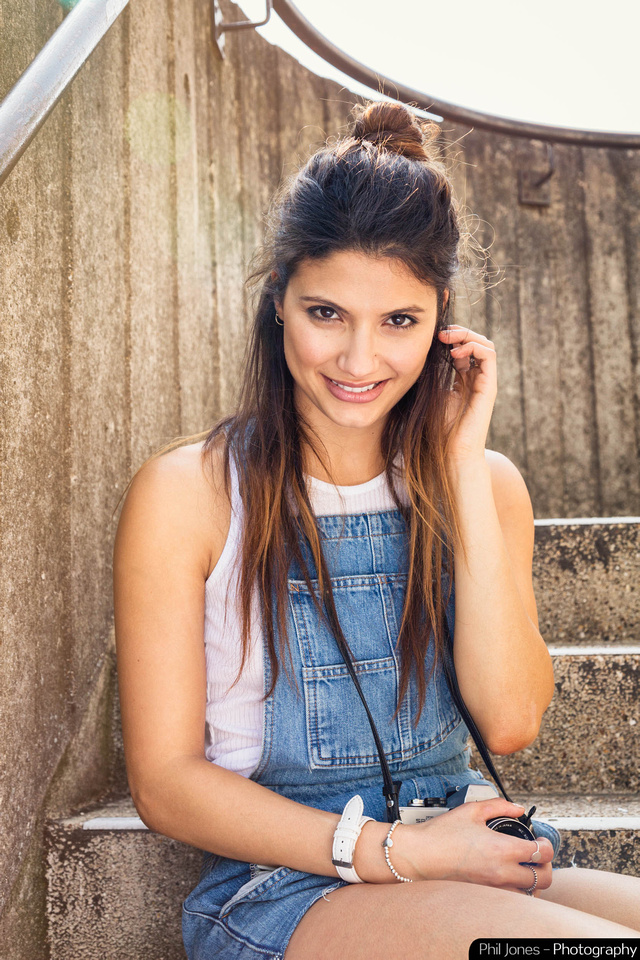 Young woman sitting on concrete steps holding retro camera and wearing denim dungarees, white sleeveless top and white watch.  Image by Phil Jones Photography