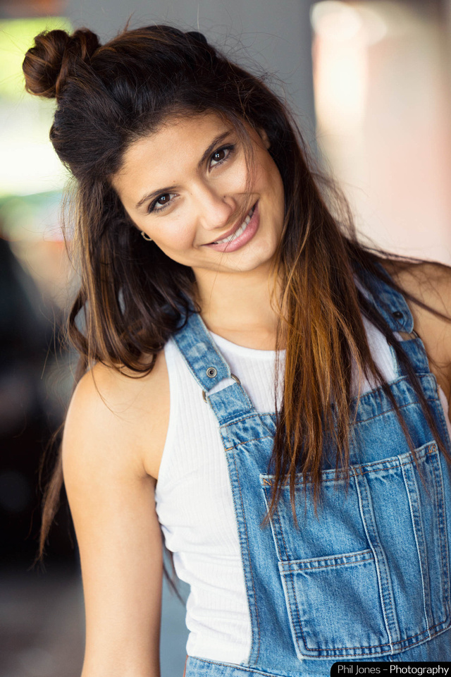 Close up photograph of smiling model wearing dungarees.  Image by Phil Jones Photography
