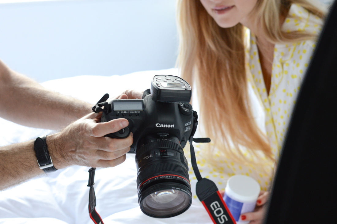 Behind the scenes shot of photographer Phil Jones showing Model Nina Clark an image on the back of his 5D mkIV