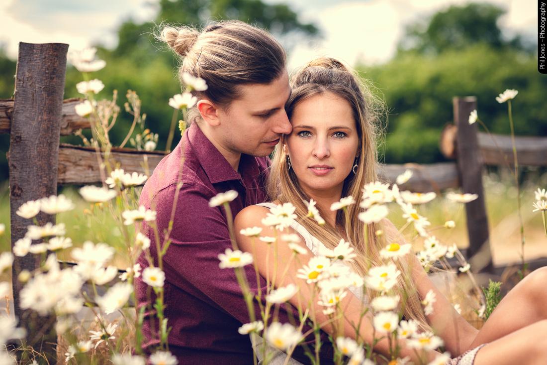 beautiful couple sitting amongst daisies at engagement photo shoot