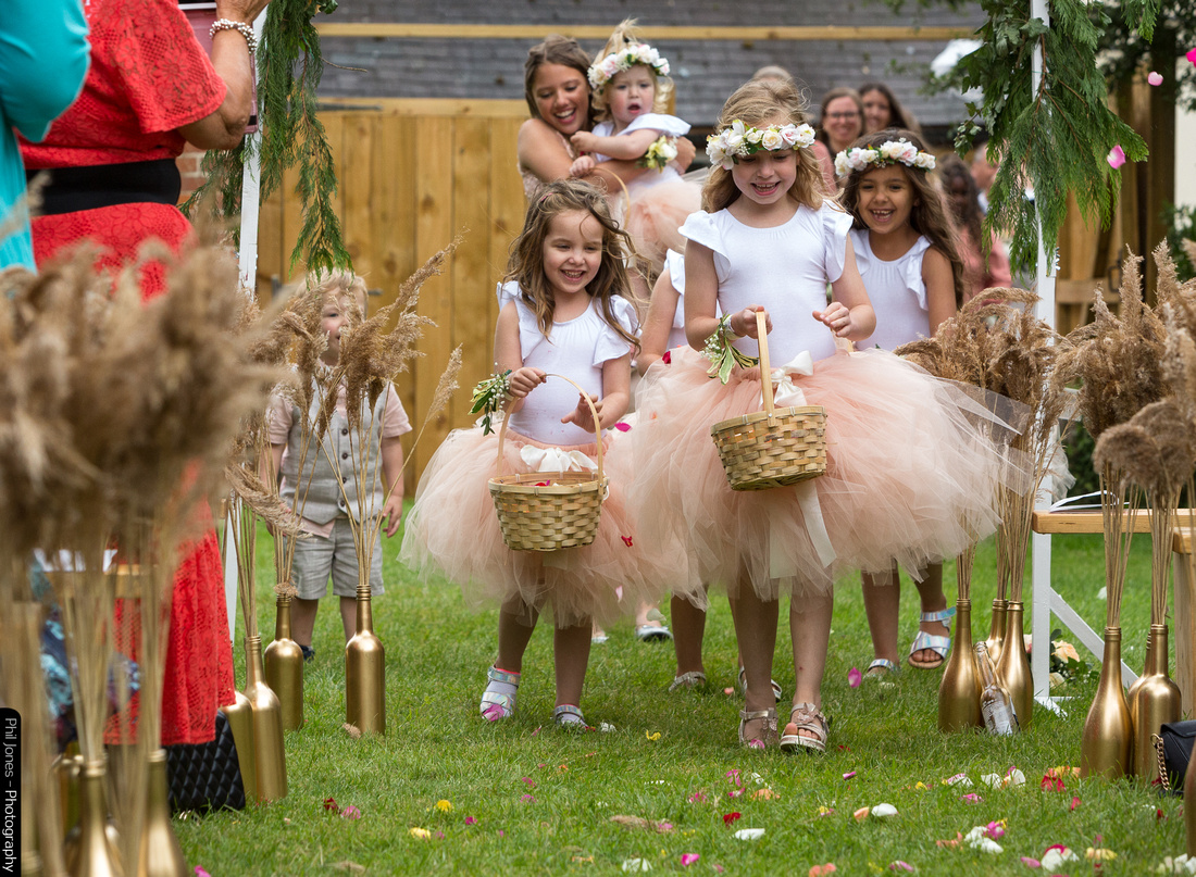 Flower girls with baskets walking down the aisle throwing petals