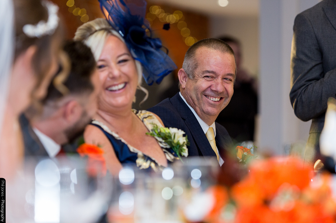 father and mother of groom laugh at wedding speech