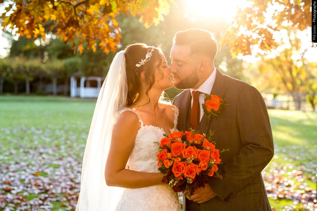Bride and groom kiss in autumn sun light
