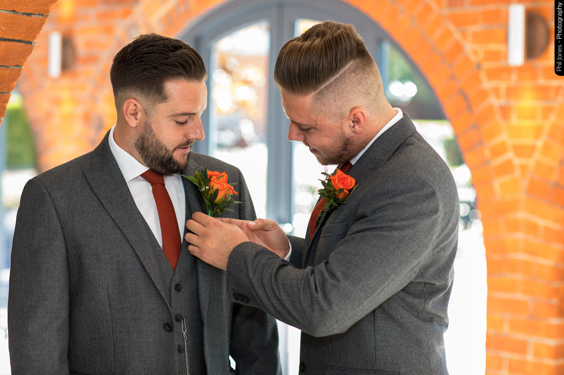Best man fixes grooms buttonhole flowers at wedding