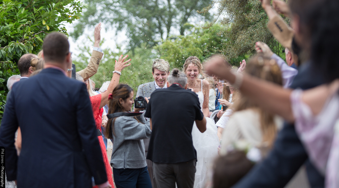 Essex wedding photographer Phil Jones as bride and groom are covered in confetti