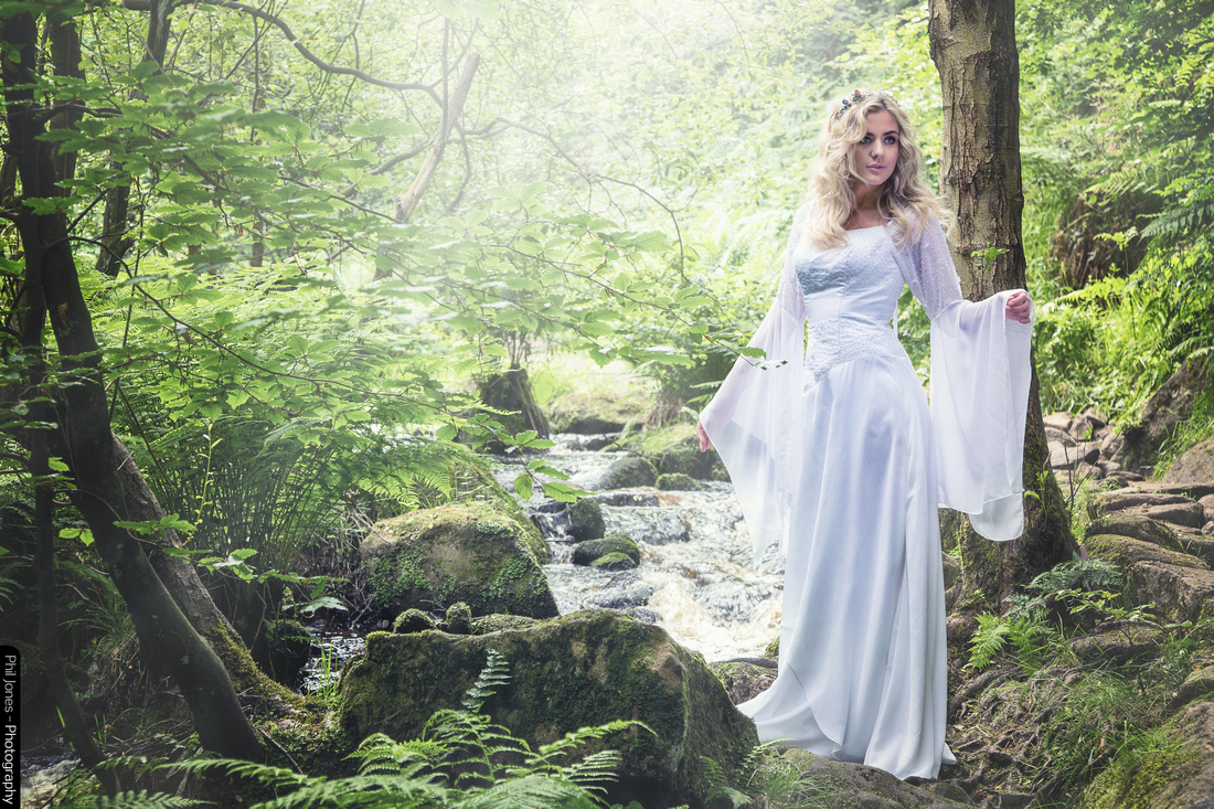 Bride in white wedding dress in a fairytale photoshoot by the brook