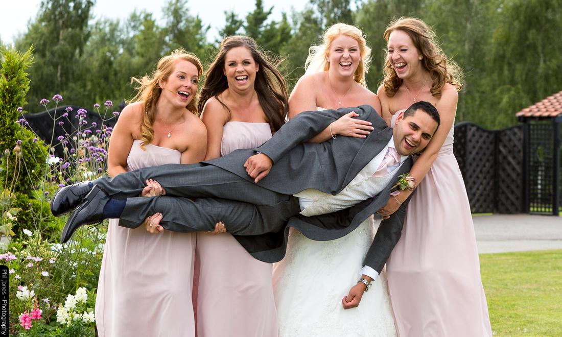 Bridesmaids hold the groom sideways during wedding photoshoot at Crondon Park, Essex