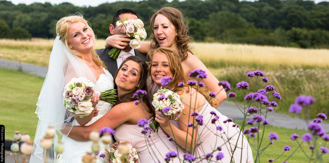 Bridesmaid covers grooms face with posy