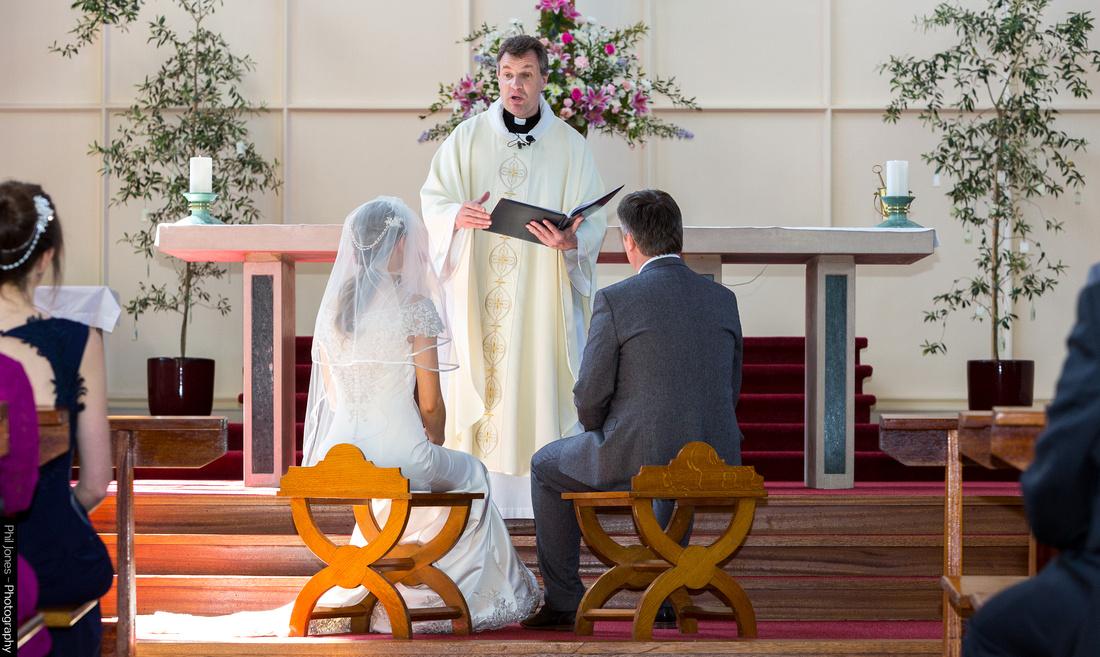 couple sit at catholic wedding in Basildon Essex