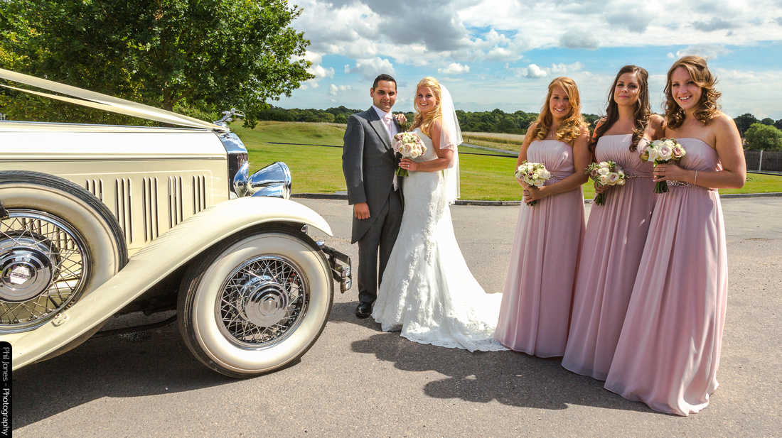 Bridesmaids standing with Bride and Groom by classic car at Essex wedding venue, Crondon Park.