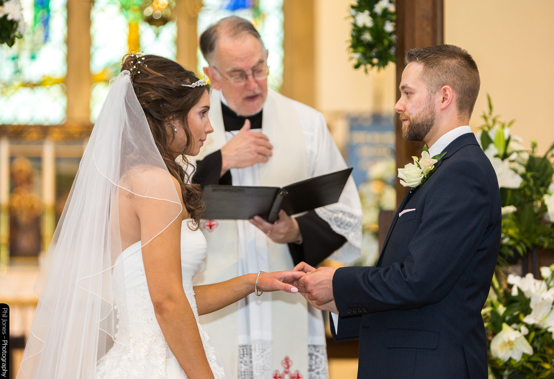 Exchange of rings at traditional church wedding ceremony Essex