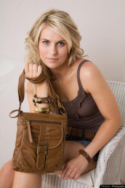 model sitting in wicker chair holding brown shoulder bag