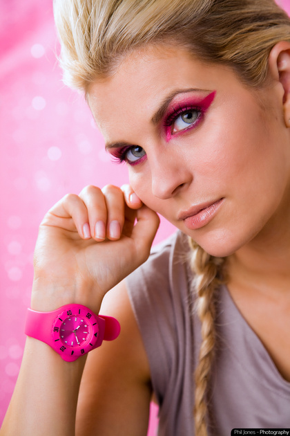 model wearing pink wrist watch inside her wrist and matching eye makeup