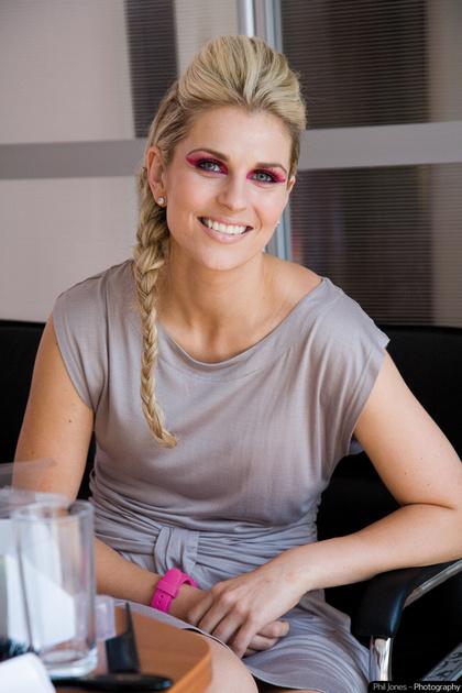 female model smiling at camera wearing pink eye makeup and matching pink wrist watch