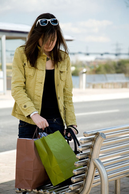 Colour coordinated lifestyle photograph of young woman with shopping bags
