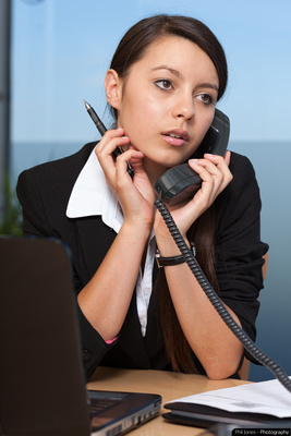 Young woman using telephone and holding pen