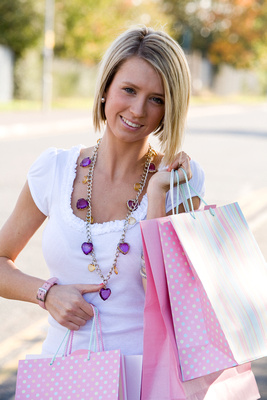 Young woman with pink shopping bags and clothing