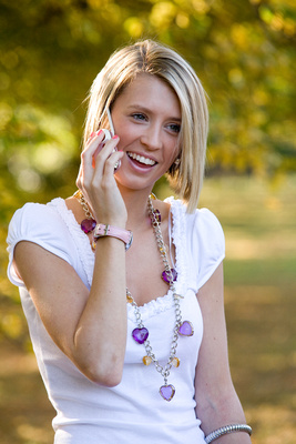 Photograph of young woman smiling using phone