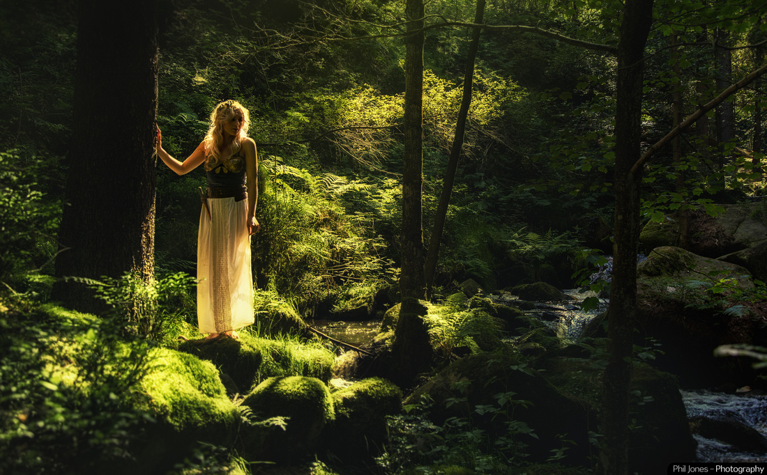 Golden light ethereal photograph of woman standing in woods