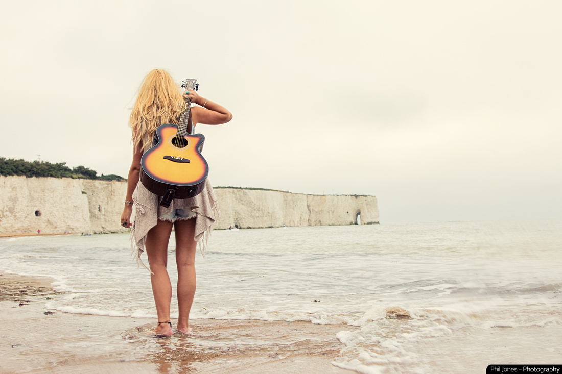 Young woman carrying guitar as she walks across the beach.