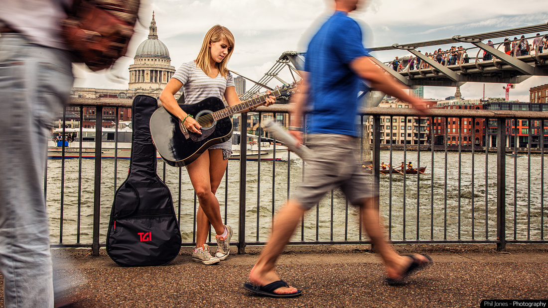 Young woman playing guitar by Millennium Bridge, London
