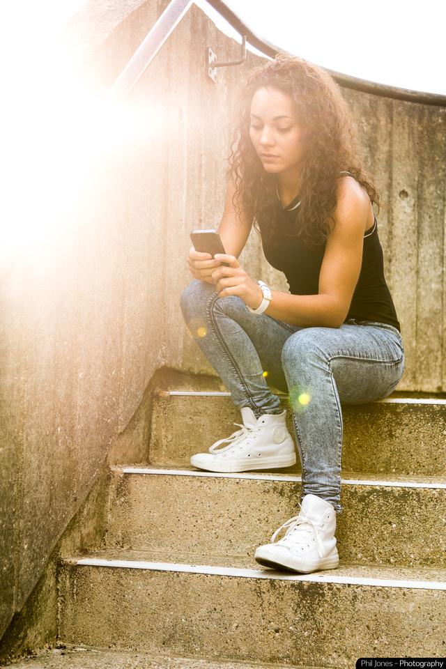 Model sitting on steps using mobile phone.