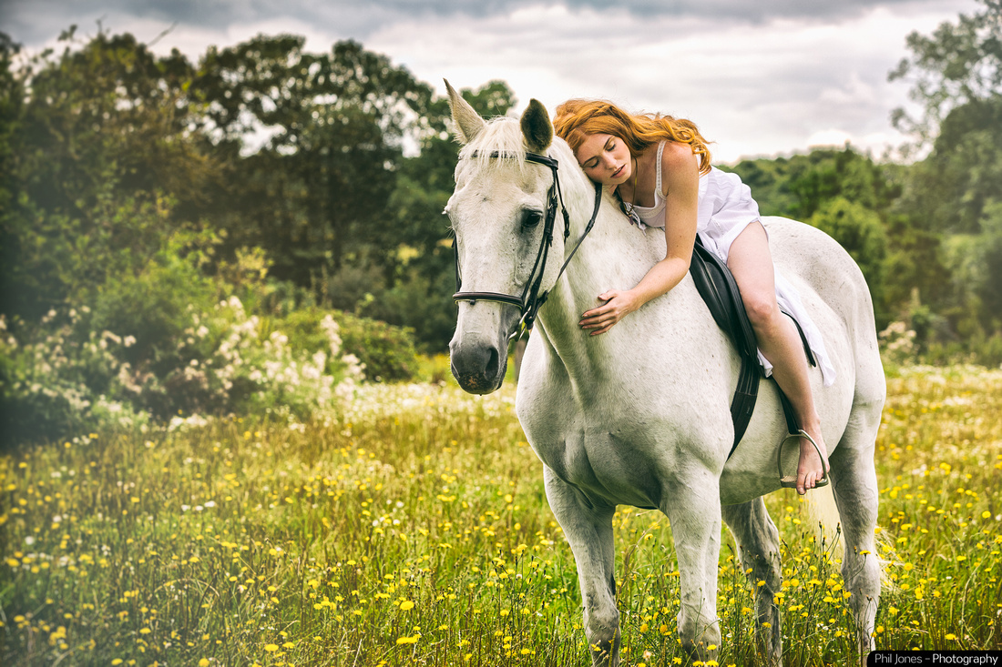 Fairytale photo shoot with beautiful woman sitting on a horse