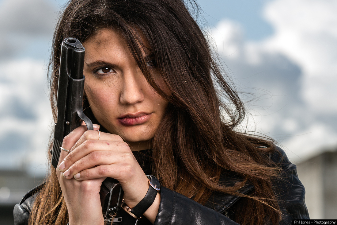 Actor Andrea Vasiliou holding hand gun on action adventure ANDIE. Photography by Phil Jones