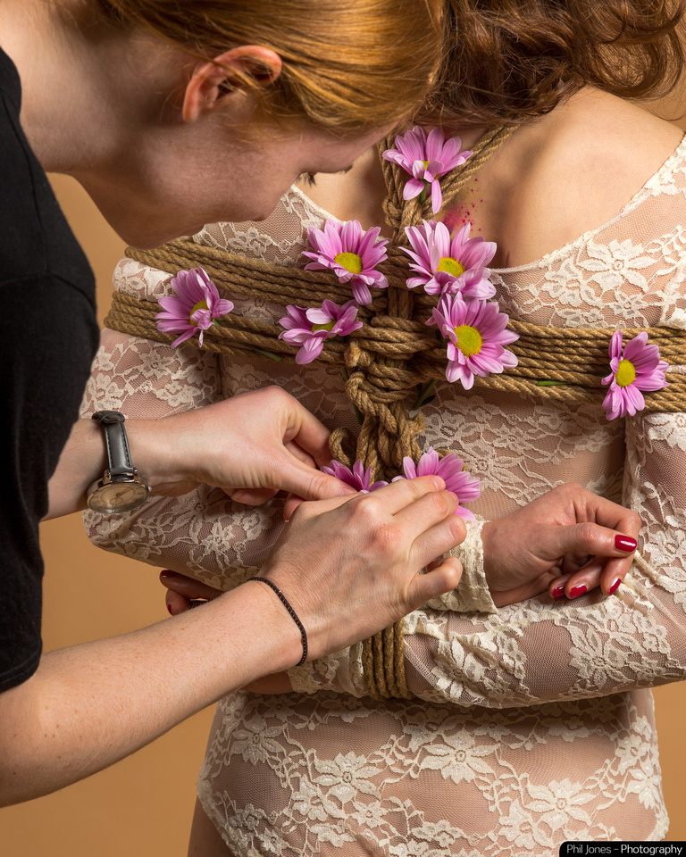 Behind the scenes Shibari photoshoot, Grace Gray adding the finishing touches to the rope tie on Anna