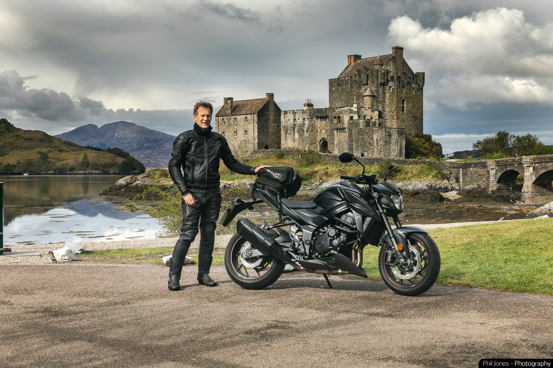 The Adventures of Phil Jones. Motorcyclist and photographer Phil Jones on Suzuki GSX S 750 at Eilean Donan Castle, Scotland