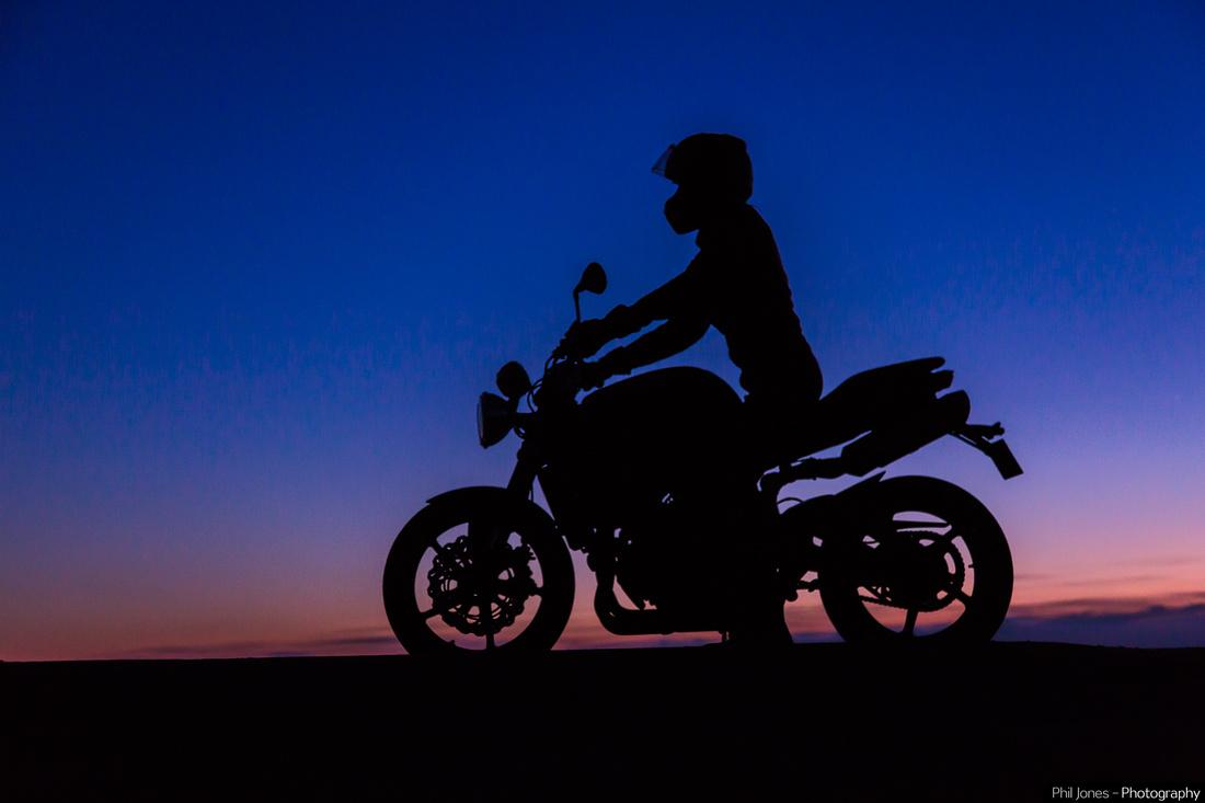 Motorcycle photography Essex. Silhouette of lady biker against the night sky