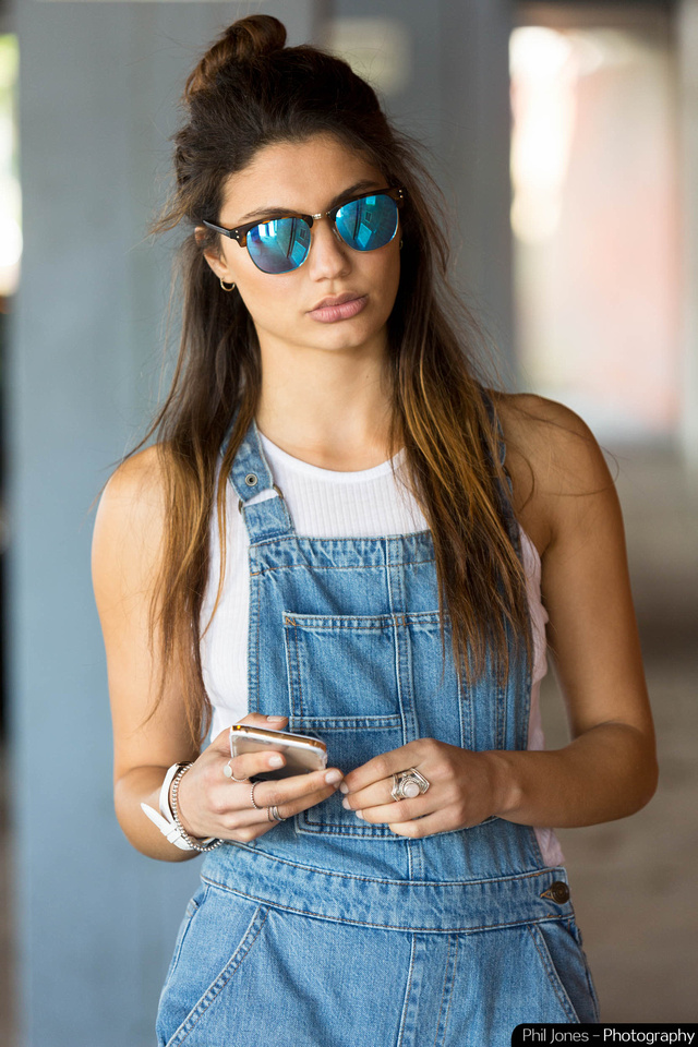 Model wearing denim dungarees, white sleeveless top, reflective sunglasses and holding iPhone.  Image by Phil Jones Photography
