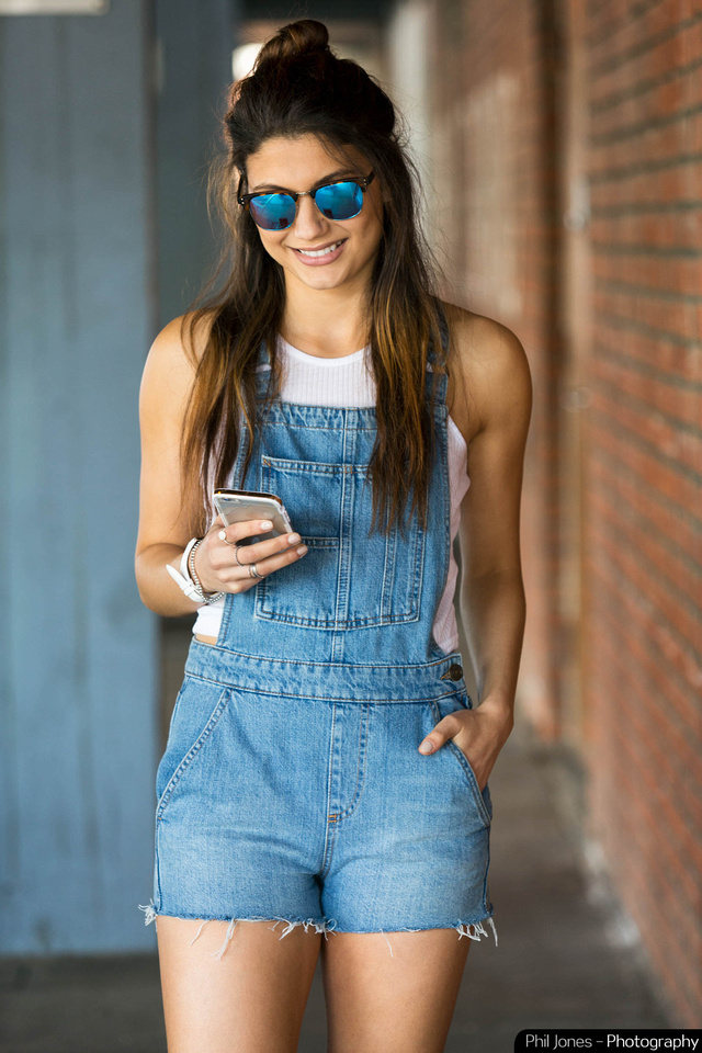 Fashion image of smiling model wearing reflective sunglasses, denim dungarees, white sleeveless top, white watch and holding iPhone.  Image by Phil Jones Photography