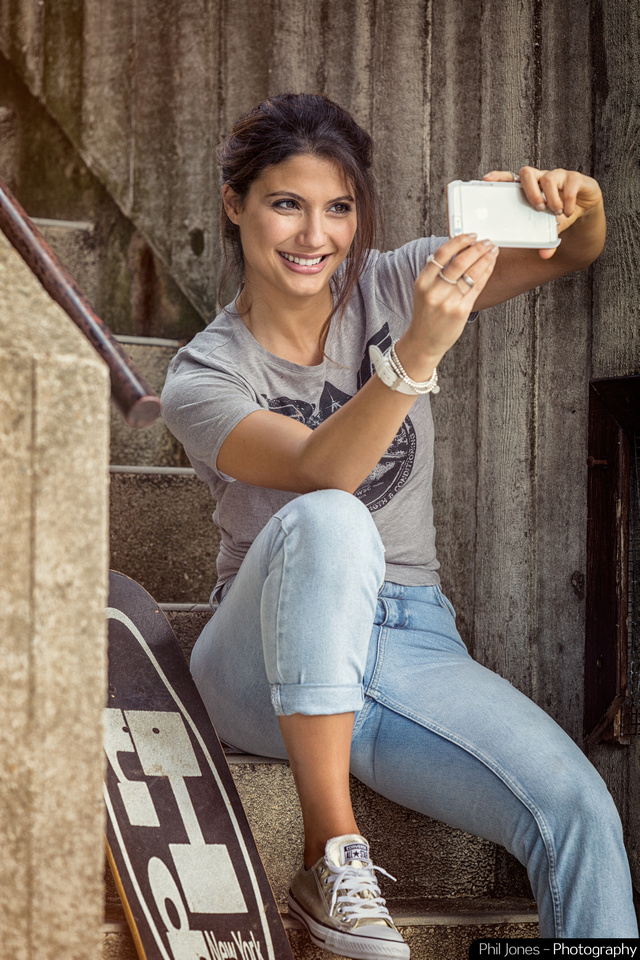 photograph of model sitting on steps holding iPhone taking a selfie. Wearing grey t-shirt, jeans and converse footwear.  Image by Phil Jones Photography