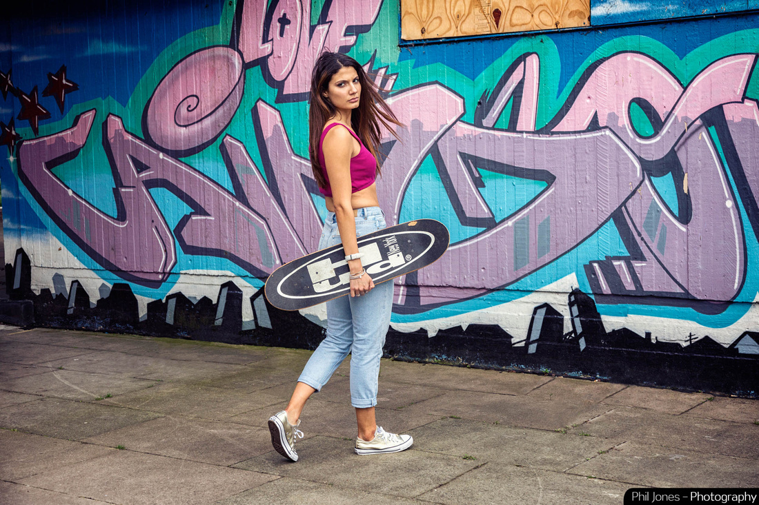 Full length photograph of model leaning against a graffiti wall wearing sports top, converse footwear, jeans and holding a skateboard.  Image by Phil Jones Photography