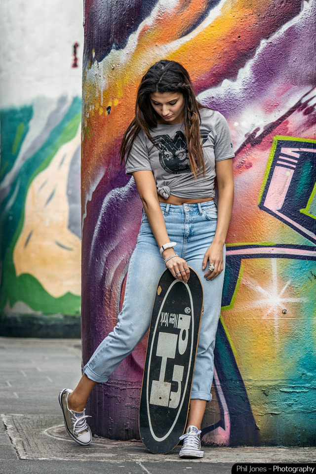 Full length photograph of model leaning against a graffiti wall wearing grey T-Shirt, converse footwear, jeans and holding a skateboard.  Image by Phil Jones Photography